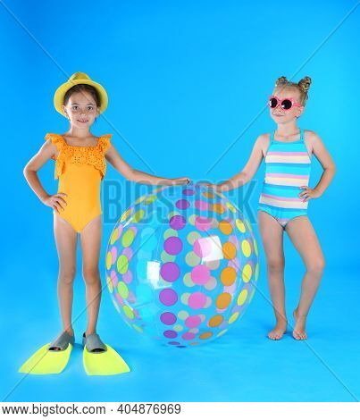 Cute Little Children In Beachwear With Inflatable Ball On Light Blue Background