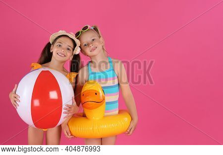 Cute Little Children In Beachwear With Bright Inflatable Toys On Pink Background. Space For Text