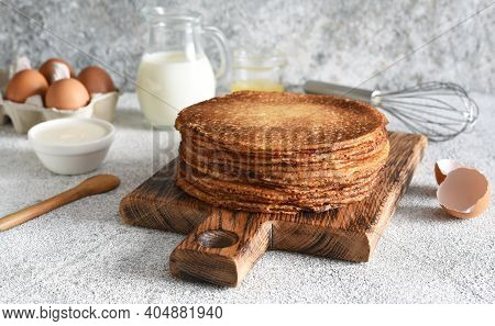 Stack Of Thin Pancakes On A Wooden Board. Pancake Ingredients: Flour, Milk, Eggs, Whisk On The Kitch