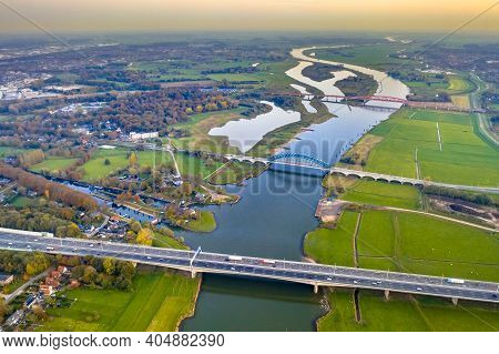 Aerial View Of Huge Lowland River Ijssel With Highway And Railroad Bridges Through Sunset Landscape.