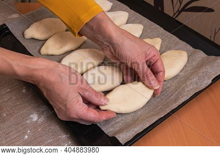A Woman Lays Out Raw Russian Pies With Filling On A Baking Sheet For Baking In The Oven. Homemade Ba