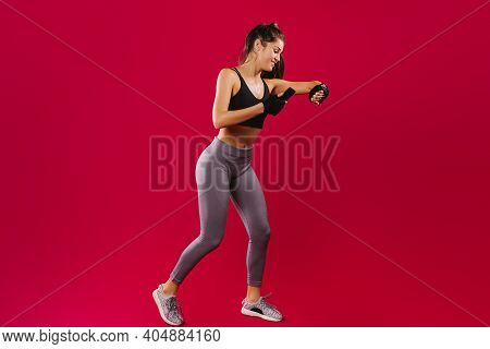 Fitness Girl In Sportswear During Training Observes Her Results On A Fitness Bracelet And Smartphone
