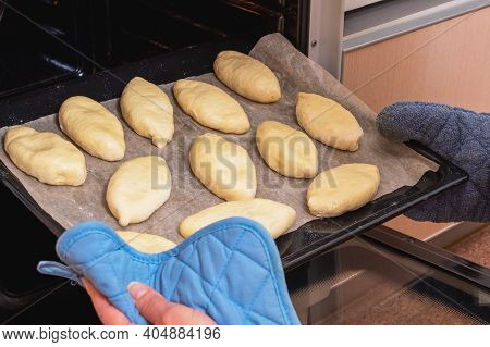 A Woman Puts Russian Pies Made Of Raw Dough With Filling Into The Oven For Baking. Homemade Baking.