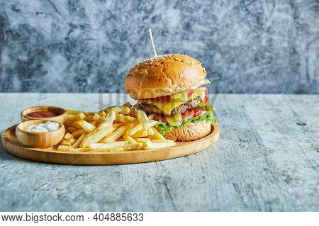 A Wooden Plate Full Of Burger, Fry Potato With Ketchup And Mayonnaise On The Marble Background