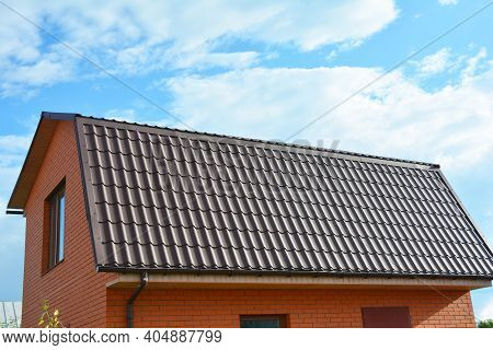 A Close-up Of A Mansard Metal Roof With An Attic Window And Roof Gutters Of A Brick House Constructi