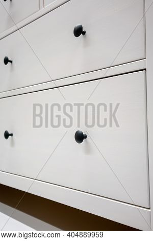 Black Circle Handle On White Drawers With Depth Of Field. Vintage Style Furniture.