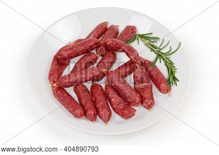 Small Thin Dry Cured Sausages In Natural Casing On A White Dish With Fresh Rosemary Twig  On A White
