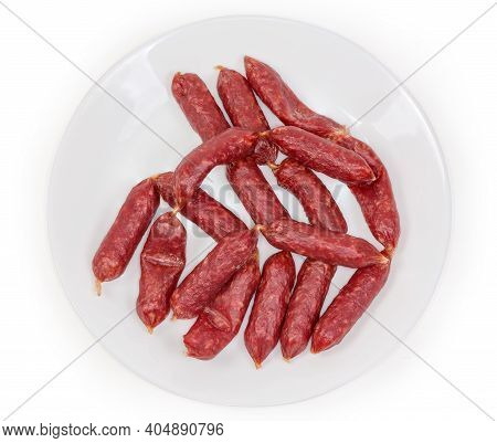 Small Thin Dry Cured Sausages In Natural Casing On A White Dish On A White Background, Top View