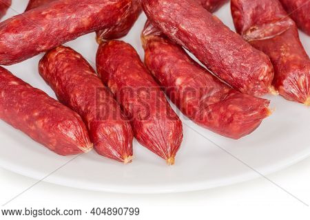 Small Thin Dry Cured Sausages In Natural Casing On A White Dish, Fragment Close-up In Selective Focu