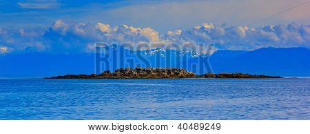 A Seascape Of Frederick Sound, Alaska With Small Rocky Island And Mountains With Clouds On The Backg