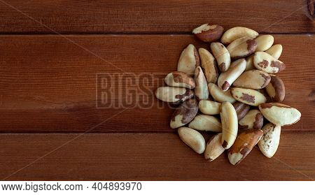 Heap Of Brazil Nuts On The Old Wooden Background Close Up Top View. Brazil Nuts From Bertholletia Ex