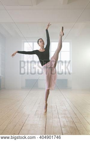 Portrait of beautiful ballet dancer stretching her leg during ballet dance in dance studio