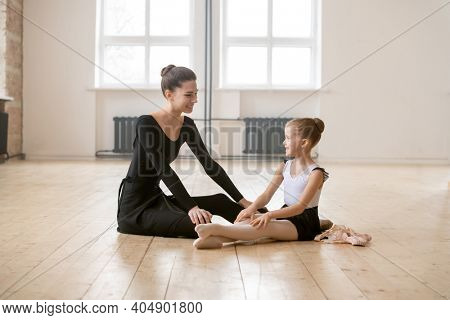 Little ballerina sitting on the floor and talking to her ballet teacher they resting after training