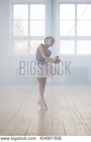 Cute little girl dreaming to become professional ballet dancer in a classical dance school