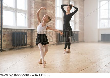 Little girl in tutu dress learning to dance the ballet together with young woman in dance studio