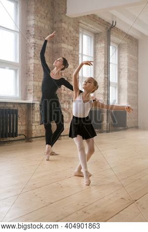 Young woman together with little girl dancing ballet during their training in dance studio