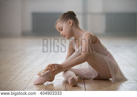 Little ballerina sitting on the floor and preparing for the classes in dance studio