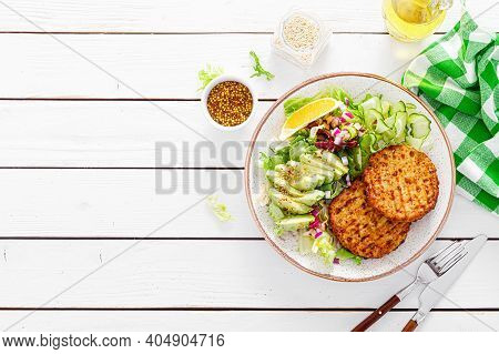 Buddha Bowl Dish With Grilled Chicken Burgers, Cucumbers, Avocado And Fresh Lettuce Salad For Lunch,