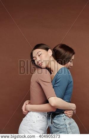 Two young beautiful female twins in casualwear standing in embrace with their eyes closed while expressing affection and love to one another