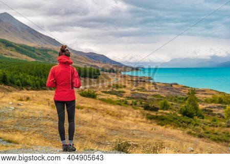 New Zealand travel - Tourist hiker on Road Trip looking at nature view of Lake Pukaki by Aoraki aka Mount Cook at Peters lookout, a famous travel tourist destination.
