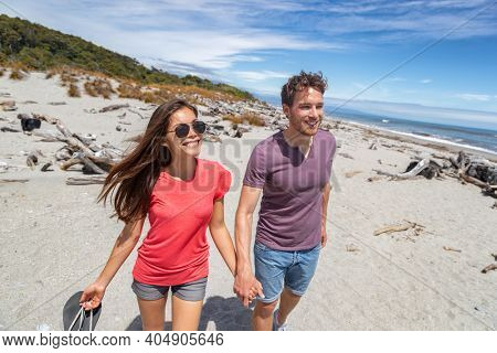 Couple walking on beach in New Zealand - people in Ship Creek on West Coast of New Zealand. Tourist couple sightseeing tramping on South Island of New Zealand.