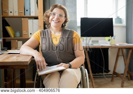 Young successful female office manager in wheelchair sitting by desk in front of camera while working with documents or planning work