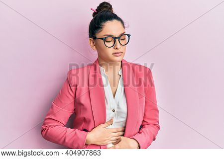 Beautiful middle eastern woman wearing business jacket and glasses with hand on stomach because indigestion, painful illness feeling unwell. ache concept.