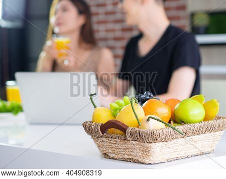 Close-up Of A Basket With Colorful Fruits In The Basket Placed On The Dining Table In The Kitchen. A