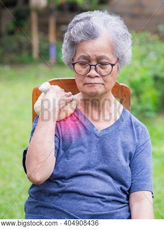 A Senior Woman Having Shoulder Pain Uses A Thai Herbal Compress Ball On The Shoulder. An Old Woman W