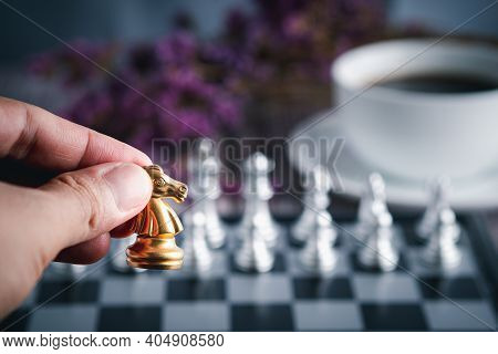 Close-up Of Hand Holding A Gold Knight On A Chessboard With A White Coffee Cup Blur Background. Busi