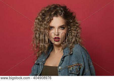 Beautiful Woman With Curly Hair. Caramel Balayage Highlights Coloring