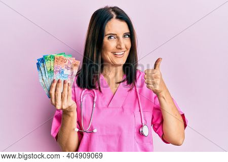 Middle age brunette doctor woman holding swiss francs smiling happy and positive, thumb up doing excellent and approval sign