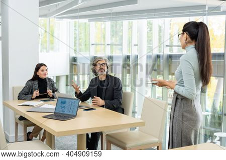 Two modern elegant economists looking at their Asian female colleague during discussion of graphic financial data at meeting in office