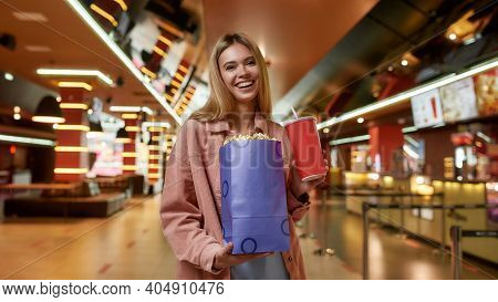 Portrait Of Excited Young Woman Holding Big Popcorn Bag And Soda While Posing In Front Of A Concessi