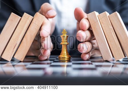 Business Man Hand Protect Chess King Figure And Stopping Falling Wooden Blocks Or Dominoes. Business