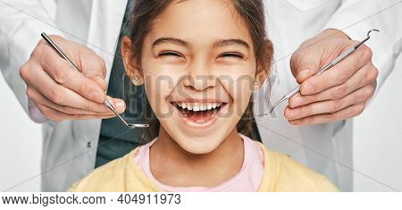 Smiling Mixed Race Girl In A Dental Clinic For Children. Child With A Toothy Smile During Inspection