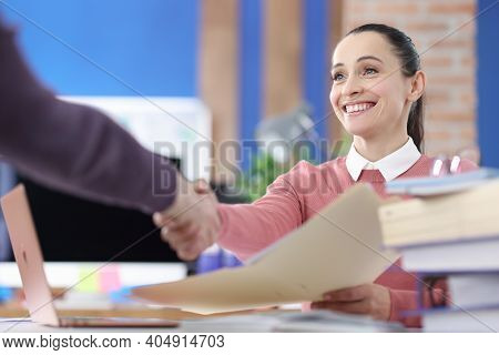 Smiling Businesswoman Shakes Hands With Business Partner. Business Arrangement And Signing Agreement