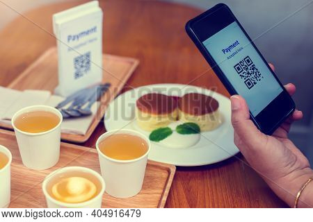 Hand Using Smart Phone To Scan Qr Code On Tag With Blurry Dessert And Tea In Coffee Shop To Accepted