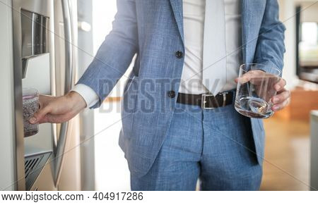 Young man in a suit pouring cold water and ice cubes from dispenser of a home fridge