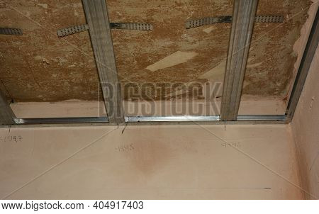 House Renovation And Drywall Ceiling Installation: A Close-up Of Metal Stud Framing On Plastered And