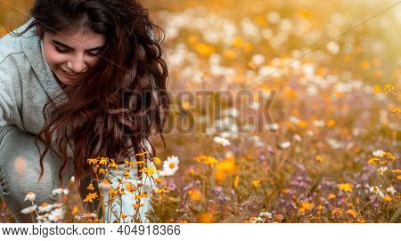 Portrait of a Cute Teen Girl with Joy Collecting Wild Flowers in Bouquet. Spending Spring Holidays in Countryside. Enjoying Fresh Springtime Nature.