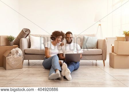 Young Black Family Couple Using Laptop Sitting On Floor Indoor After Moving New Home. Real Estate, H