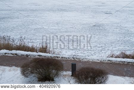 Embankment Of A Frozen City Lake With Many Footprints On Ice, Cloudy