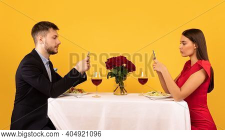 Boring Date. Couple Using Cellphones During Dinner Sitting At Table Posing Over Yellow Background In