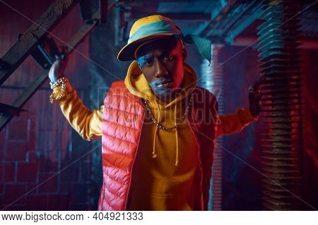 Stylish rapper in yellow hoodie posing in studio