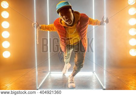 Stylish rapper on the stage with illuminated cube