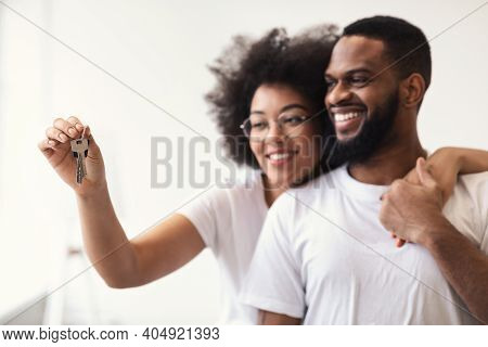 Happy African American Couple Holding New House Key Hugging Standing At Home. Property Purchase And