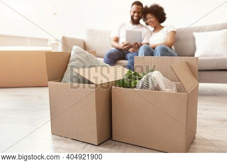 Moving Boxes Standing On Floor While Happy Black Couple Using Digital Tablet Packing For A House Mov