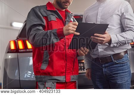 Crop Unrecognizable Mechanic Making Notes In Checklist While Discussing Problems With Client In Car
