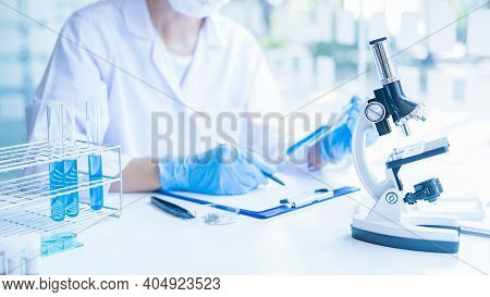 Medical Or Scientific Researcher Or Man Doctor Looking At A Test Tube Of Clear Solution In A Laborat